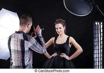 Top model and photographer - Top model in black dress posing...
