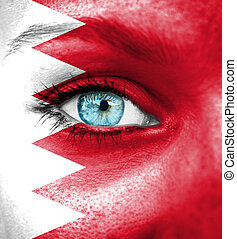 Woman face painted with flag of Bahrain