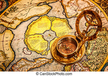 Vintage still life. Vintage compass lies on on the ancient...