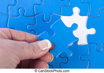 Close up of womans hand placing missing piece in Jigsaw...