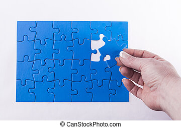 Womans hand placing missing piece in Jigsaw puzzle...