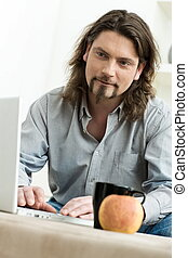 Man using laptop computer - Casual man using laptop computer...
