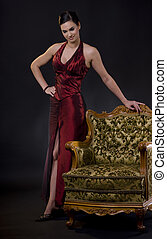 Woman posing with arm chair - Beautiful young woman wearing...