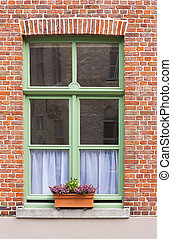 Traditional brick house window with window box in Bruges,...
