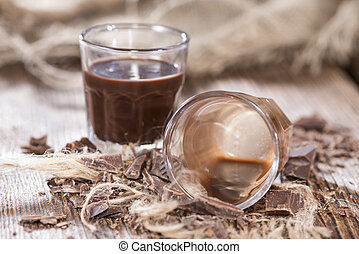 Chocolate Liqueur (homemade) on a dark vintage wooden table