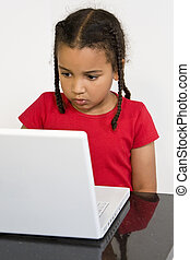 Little Girl Using A Laptop Computer - A beautiful young...