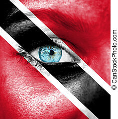 Woman face painted with flag of Trinidad and Tobago