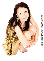 Woman sitting in gold dress - Woman sitting and holding her...