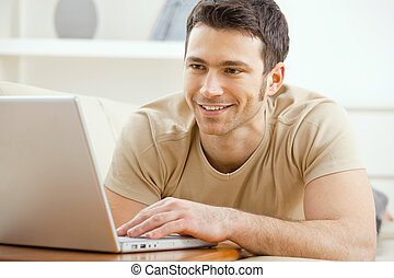 Man using laptop at home - Happy young man laying on sofa at...