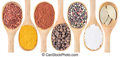 Collection of 7 spices on a wooden spoon isolated on a white...