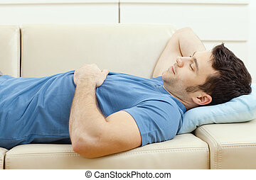 Man sleeping on couch - Young handsome man sleeping on couch...