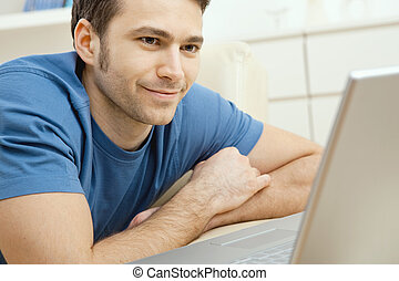 Young man using laptop at home - Happy young man laying on...