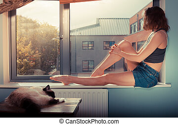 Young woman on window sill with cat - A young woman is...