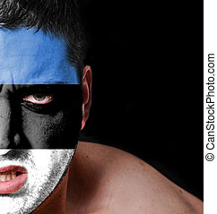Portrait of angry man with painted flag of Estonia