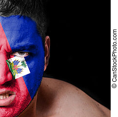 Portrait of angry man with painted flag of Haiti
