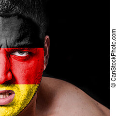 Portrait of angry man with painted flag of Germany