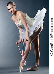 Charming female ballet dancer posing tying pointe in studio