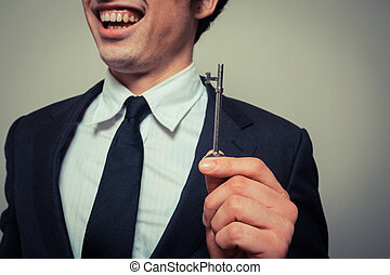Happy young businessman with key - Happy young businessman...