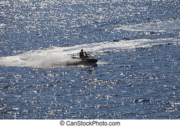 Man on Wave Runner in sparkling sea - Man riding jet ski in...