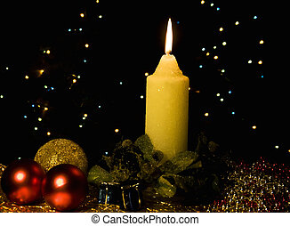 Burning candle with Christmas-tree decorations against a...