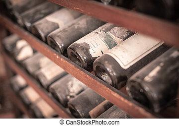 Dusty bottles - a lot of very old dusty wine bottles in an...