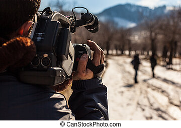 Reportage - a young man using a professional camcorder...