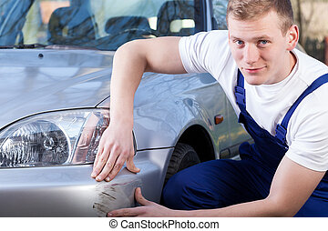 Mechanic repairing car scratching - Handsome mechanic during...