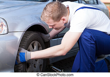 Mechanic changing car wheel - Mechanic during changing car...