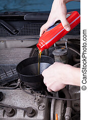 Pouring motor oil - Mechanic during pouring motor oil in...