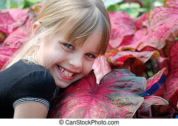 Back To Nature - Blonde child with plants in a greenhouse.