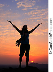 Sillouetted woman with her arms up at sunset on top of the...