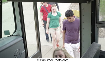 Kids students getting on bus - High school kids getting on a...