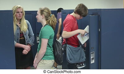 Students visiting locker in school - High school kids...