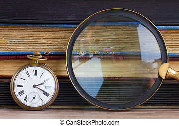 antique clock with loupe  on books background