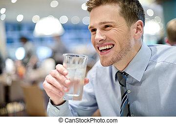 Smiling young man drinking water in cafe - Handsome young...