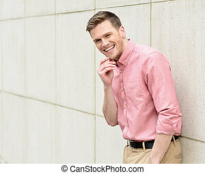 Happy young man standing against wall - Handsome businessman...