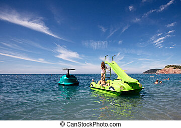 pedal boat - Young boy and girl having fun on a pedalling...