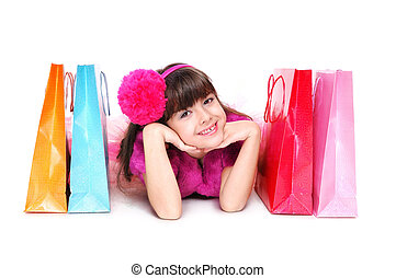 girl laying on the floor and paper shopping bags next to her