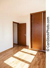 Empty room with door and wardrobe