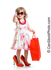 Funny kid girl trying on her moms red accessories and shoes