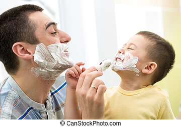 playful father and his son shaving and having fun in...