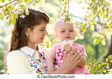 Allergy. Mother and baby blowing nose outdoors