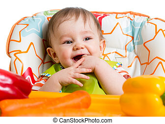 smiling baby sitting in chair ready to eat