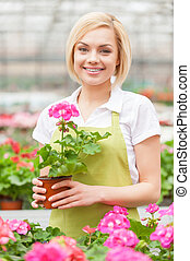 It is my favorite flower. Beautiful young woman in apron...