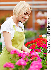 She loves her job. Beautiful blond hair woman in apron arranging flowers and smiling