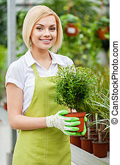Enjoying her work with plants. Beautiful young woman in...