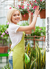 I love flowers. Beautiful blond hair woman in apron arranging flowers and smiling