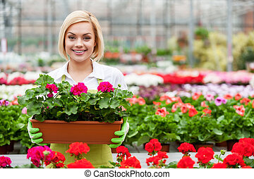 Working with flowers. Beautiful blond hair woman holding a...