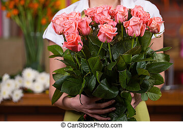 Women with bunch of roses Cropped image of woman holding...