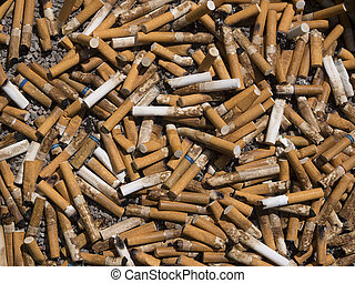 Cigarette butt background - closeup of many dirty cigarettes...